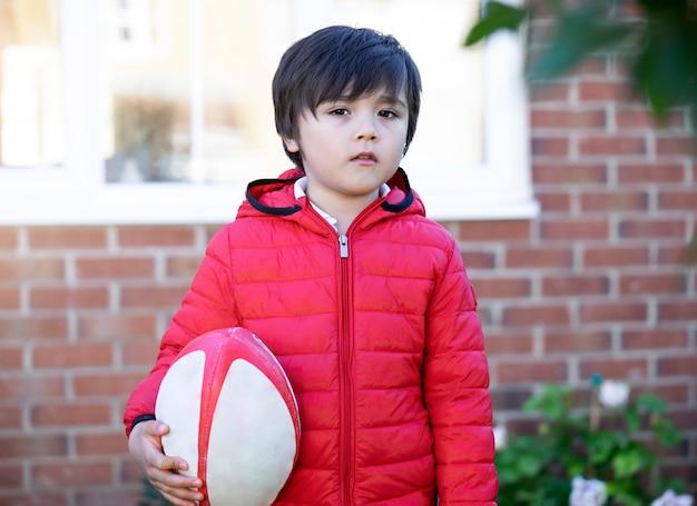 Kid garçon avec sourire jouant au rugby en journée ensoleillée matin, printemps ou été sport pour jeunes enfants