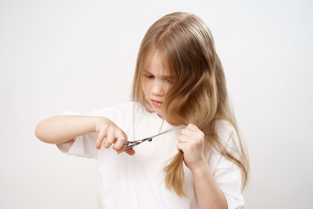 Kid girl cisaille les cheveux longs avec des ciseaux et peur sur fond blanc. coupe de cheveux à la mode
