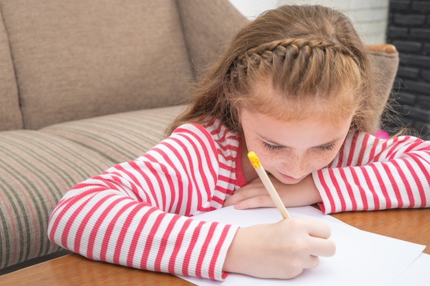 Kid girl est un crayon à colorier sur papier dans le salon