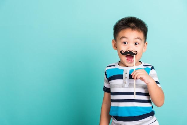 Kid hipster drôle tenant des accessoires de moustache noire pour le photomaton fermer le visage
