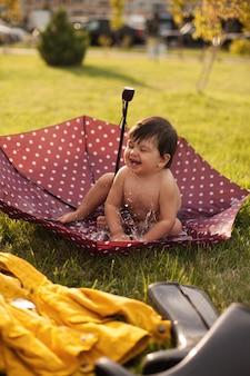 Kid joue et éclabousse dans l'eau assis dans un parapluie. un imperméable et des bottes en caoutchouc se trouvent côte à côte dans l'herbe.