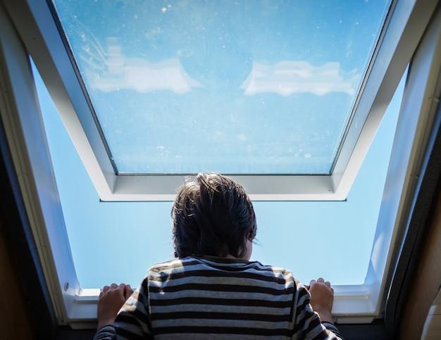 Kid à la maison fenêtre d'ouverture