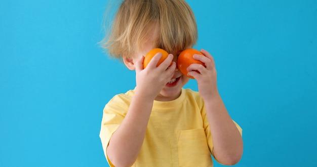 Kid avec des mandarines. petit garçon avec des mandarines