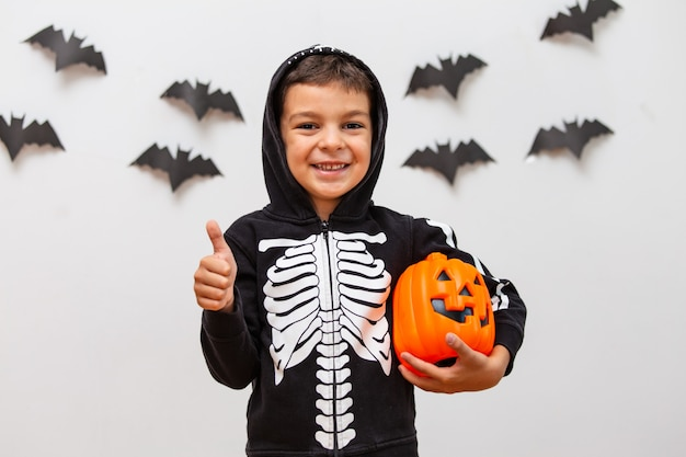 Kid mignon en costume d'halloween posant avec citrouille.