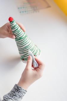 Kid montre une décoration d'arbre de noël. fabrication d'arbre de noël créatif à la main. concept de bricolage pour enfants. faire la décoration de jouets de noël décorer le jouet avec des strass arbre de noël écologique