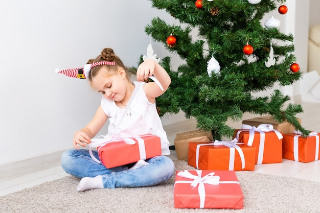 Kid ouvrant des cadeaux de noël. enfant sous l'arbre de noël avec des coffrets cadeaux.