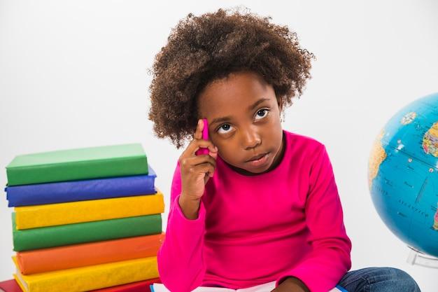 Kid pensant assis avec des livres en studio