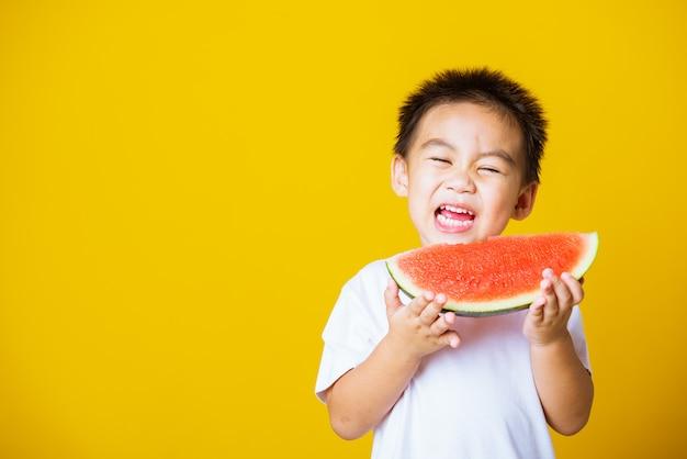 Kid petit garçon sourire détient pastèque coupée fraîche pour manger