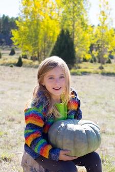 Kid petite fille hoding citrouille d'halloween en plein air