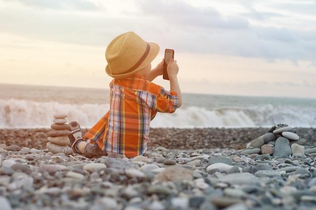 Kid photos au téléphone assis sur la plage