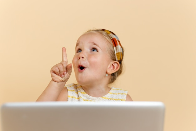 Kid pointer le doigt vers le haut beige isolé