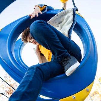 Kid s'amusant sur l'aire de jeux en plein air