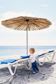 Kid se penche sur une chaise longue sous un parasol au toit de chaume et regarde la mer