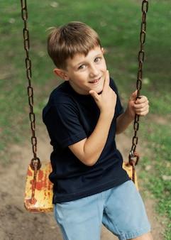 Kid shot moyen assis sur la balançoire