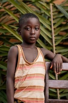 Kid shot moyen posant avec chaise
