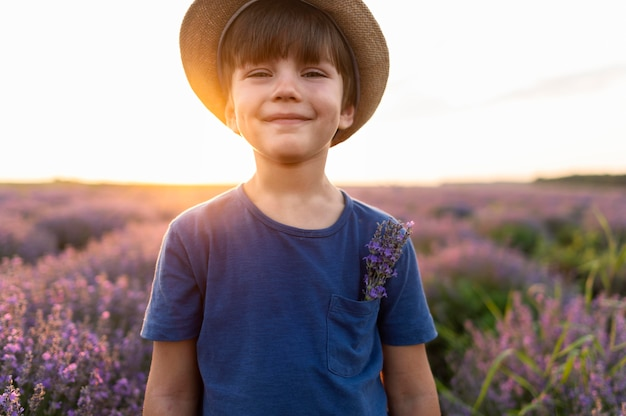 Kid shot moyen posant dans un champ de fleurs