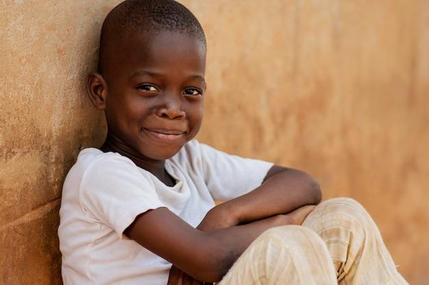 Kid smiley coup moyen assis à l'extérieur