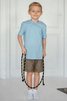 Kid smiley tir complet tenant la corde à sauter