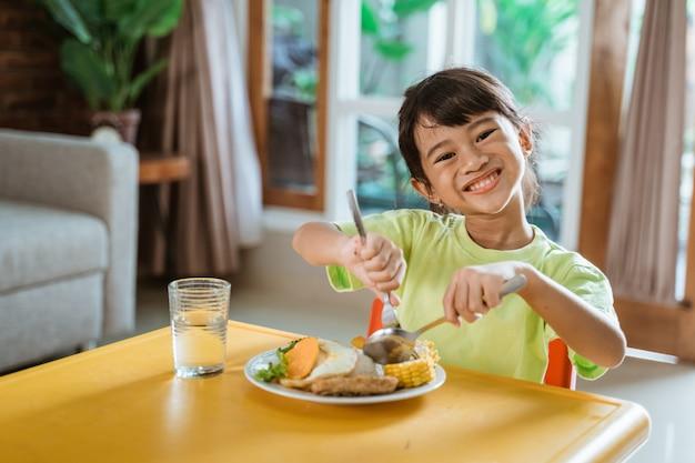 Kid souriant tout en prenant un petit déjeuner sain