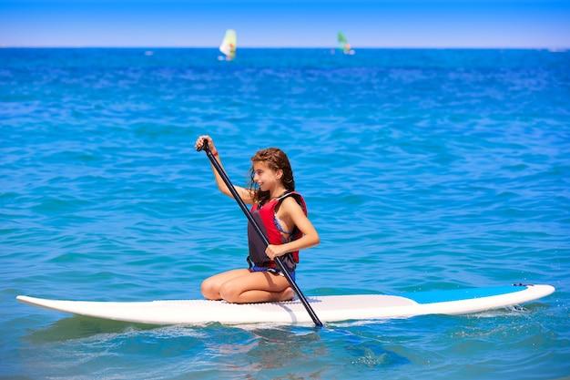 Kid surf surfer fille avec rangée sur la plage