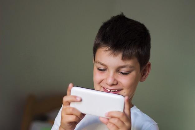 Kid utilisant un téléphone intelligent mobile et souriant