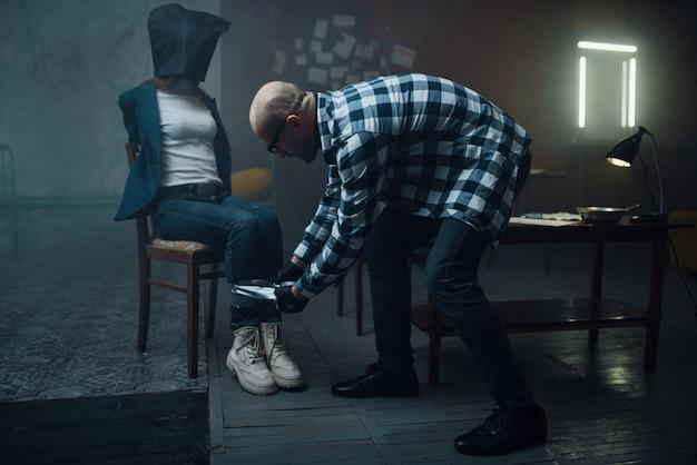 Un kidnappeur maniaque tape sur les jambes de sa victime. l'enlèvement est un crime grave, un psychopathe fou, un kidnapping horreur, de la violence