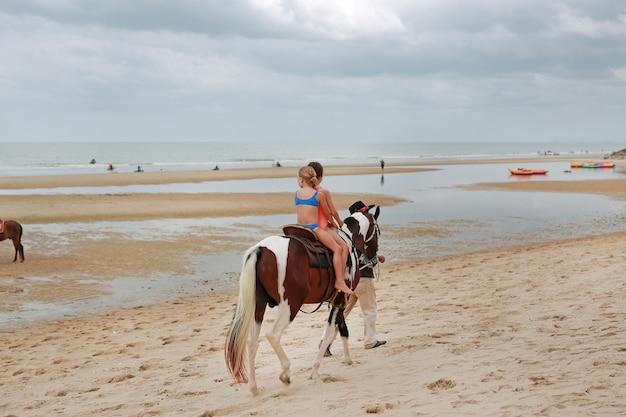 Kids fille monte à cheval sur la plage. huahin thaïlande.
