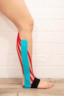 Kinesio bande femme jambe gros plan. concept de réhabilitation de vue verticale