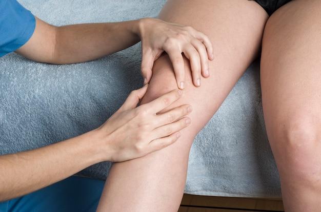 Kinésithérapeute, chiropraticien faisant une mobilisation rotulienne, douleur au genou