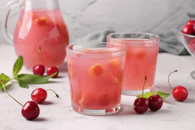 Kissel aux cerises douces dans deux verres et pichet sur fond gris, format horizontal