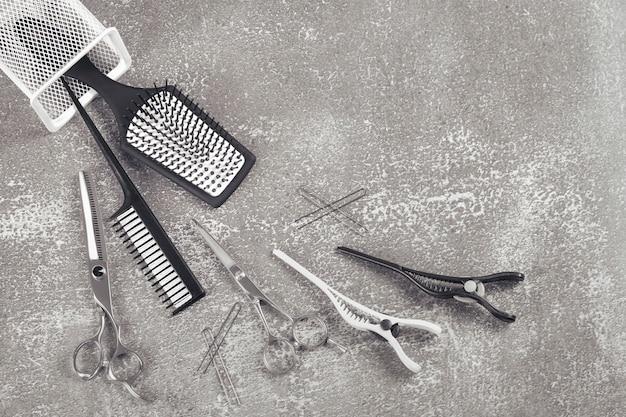 Kit coiffure, peigne ciseaux et clips sur surface gris clair