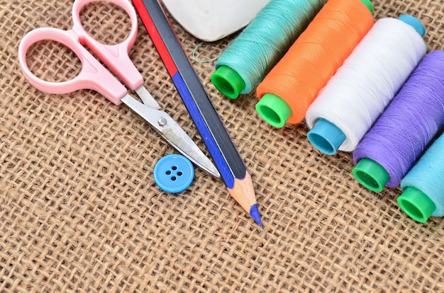 Kit de couture. ciseaux, bobines avec fil et aiguilles sur le vieux tissu