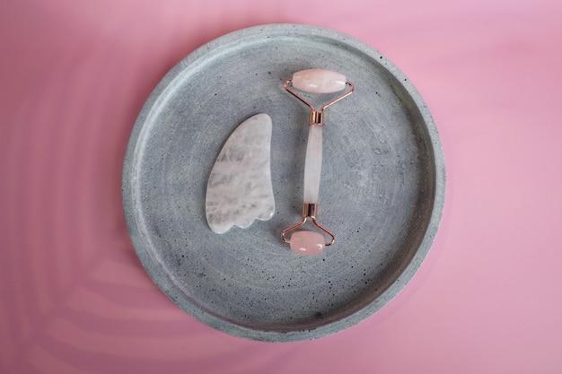 Kit de massage du visage. rouleau de visage et masseur gua sha fabriqués à partir de pierres roses naturelles, bien-être, concept de remise en forme du visage, carte monochrome élégante, bannière de luxe.