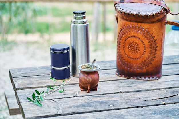 Kit maté uruguayen doublé de cuir, avec l'ampoule, thermos et sac sur une table en bois à la campagne