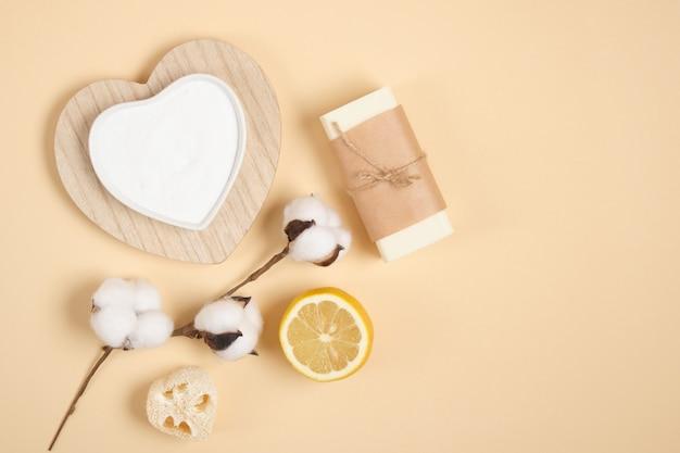 Kit de nettoyage et de soins du corps respectueux de l'environnement, citron, savon, soda, luffa, éponge et fleur de coton sur fond beige, espace de copie de vue de dessus du concept de mode de vie zéro déchet
