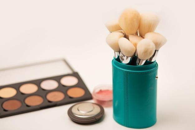Kit de pinceaux pour le maquillage du visage dans un étui, palette de contouring et poudre pressée sur fond gris