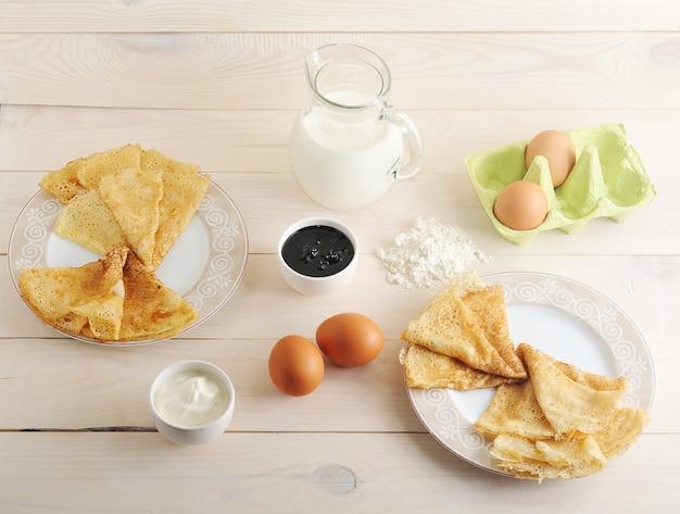 Un kit pour la fabrication de crêpes, œufs, lait, pichet, farine, crème sure et confiture