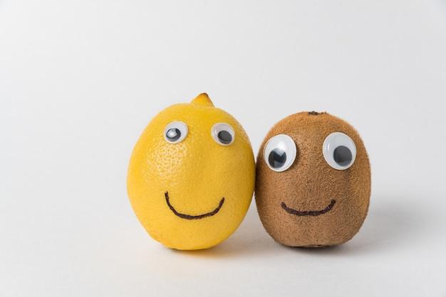 Kiwi et citron avec des yeux écarquillés et des sourires sur fond blanc. concept d'amitié
