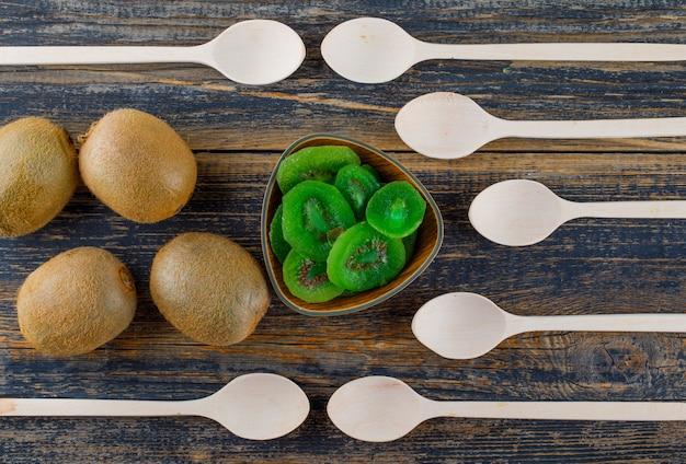 Kiwi avec cuillères, tranches séchées à plat sur un fond en bois