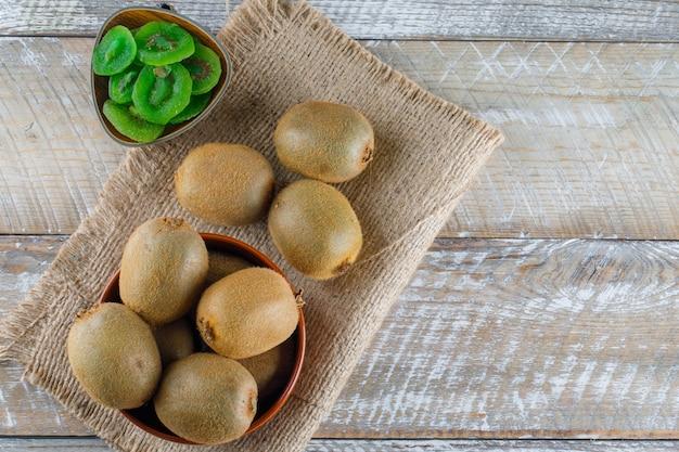 Kiwi dans un bol avec des tranches séchées à plat poser sur du bois et un morceau de sac