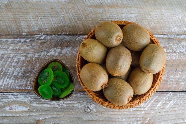 Kiwi dans un panier en osier avec des tranches séchées à plat sur une table en bois