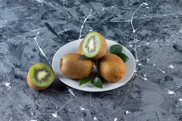 Kiwi entiers et tranchés avec des feuilles placées dans une assiette blanche.