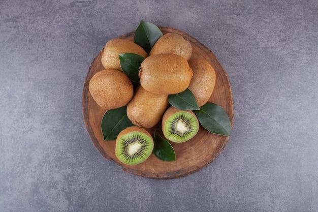 Kiwi entiers et tranchés avec des feuilles placées sur une pierre.