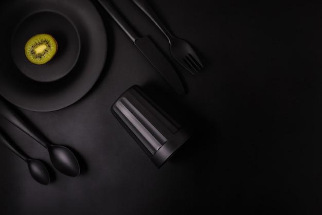 Kiwi sur fond noir avec verre noir, plaque noire, couverts noirs, vue de dessus