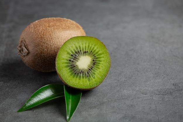 Kiwi frais, coupé en deux, posé sur un sol sombre