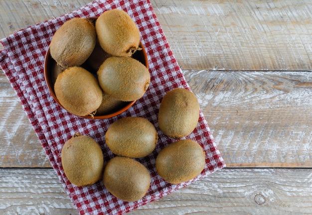 Kiwi frais dans un bol sur tissu en bois et pique-nique. pose à plat.