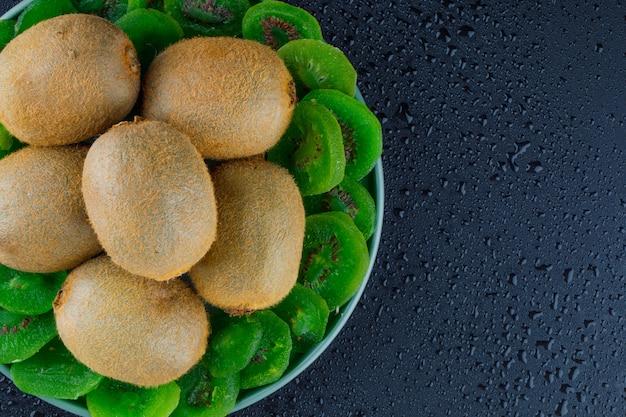 Kiwi frais avec kiwi séché dans une assiette sur fond gris foncé, pose à plat.