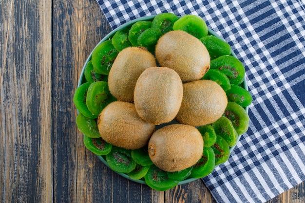 Kiwi frais avec kiwi séché dans une assiette sur fond de tissu en bois et pique-nique, pose à plat.