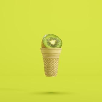Kiwi fruit avec cornet de crème glacée flottant sur fond vert
