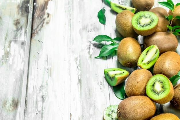 Kiwi mûr avec des feuilles sur table rustique blanche